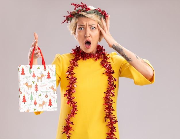 Zaniepokojona młoda blondynka ubrana w świąteczny wieniec na głowę i świecącą girlandę na szyi, trzymając worek prezentów bożonarodzeniowych patrząc na aparat, dotykając głowy na białym tle