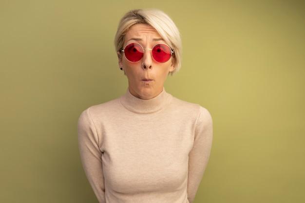 Zaniepokojona młoda blondynka w okularach przeciwsłonecznych trzymająca ręce za plecami