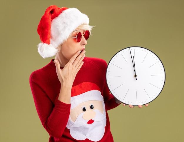 Zaniepokojona młoda blondynka w świątecznej czapce i świątecznym swetrze świętego mikołaja w okularach, trzymając rękę na ustach i patrząc na zegar odizolowany na oliwkowej ścianie