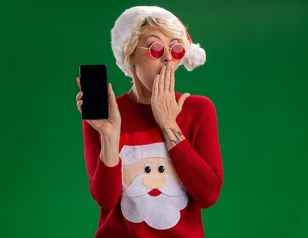 Zaniepokojona młoda blondynka w świątecznym kapeluszu i świętym mikołajowym świątecznym swetrze w okularach pokazujących telefon komórkowy trzymający rękę na ustach odizolowany na zielonej ścianie z kopią miejsca