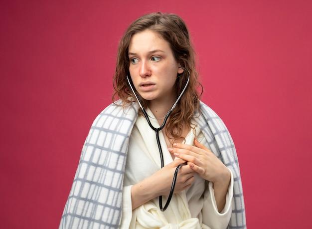 Zaniepokojona młoda chora dziewczyna, patrząc na bok, ubrana w białą szatę owiniętą w kratę i słuchająca własnego bicia serca ze stetoskopem na różowym tle