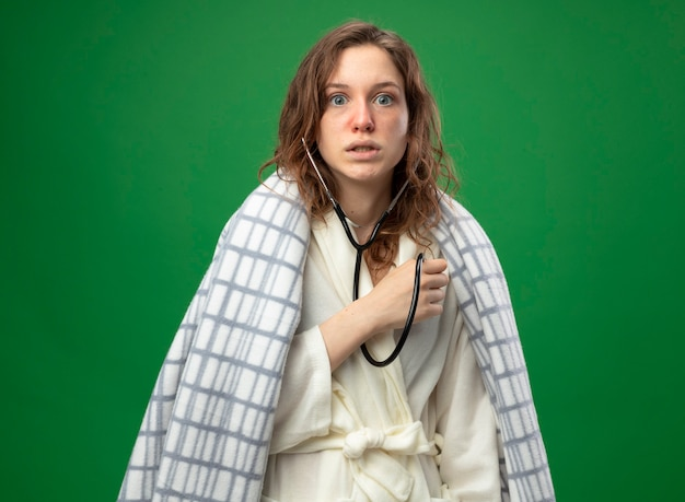 Zaniepokojona młoda chora dziewczyna ubrana w białą szatę owiniętą w kratę słuchająca własnego bicia serca ze stetoskopem izolowanym na zielono