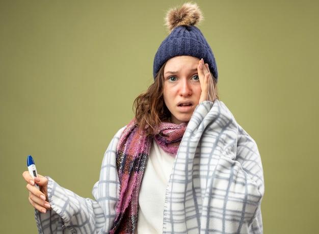 Zaniepokojona młoda chora dziewczyna w białej szacie i czapce zimowej z szalikiem owiniętym w kratę trzymająca termometr kładąca dłoń na policzku odizolowana na oliwkowej zieleni