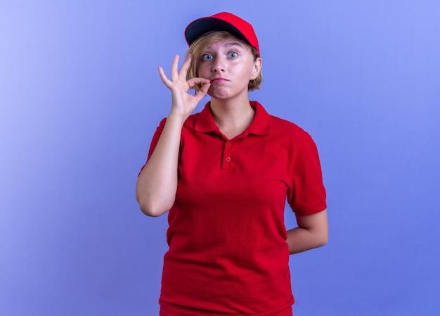 Zaniepokojona młoda dostawa dziewczyna ubrana w mundur i czapkę pokazującą gest ciszy na niebieskiej ścianie