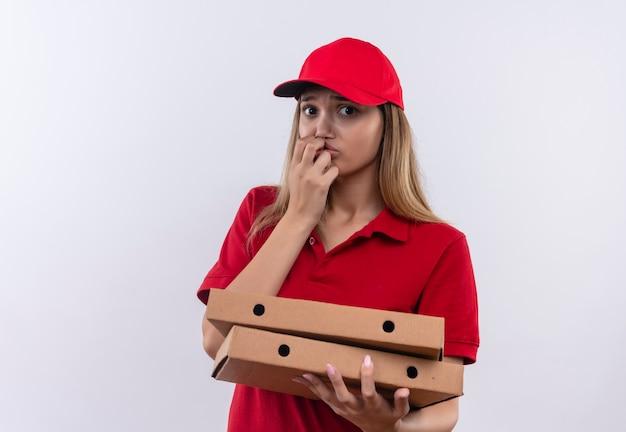 Zaniepokojona młoda dziewczyna dostawy ubrana w czerwony mundur i czapkę, trzymając pudełka po pizzy i kładąc dłoń na ustach na białej ścianie