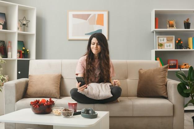 Zaniepokojona młoda dziewczyna trzyma telefon i patrzy na telefon, siedząc na kanapie za stolikiem kawowym w salonie