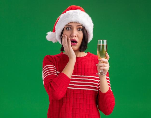Zaniepokojona młoda dziewczyna w kapeluszu santa trzymająca kieliszek szampana patrząc na kamerę trzymającą rękę na twarzy na białym tle na zielonym tle z kopią przestrzeni