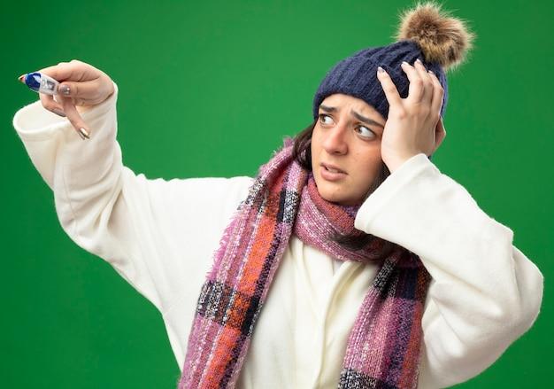 Zaniepokojona młoda kaukaska chora dziewczyna w szacie zimowej czapce i szaliku trzyma termometr i patrzy na niego, trzymając rękę na głowie odizolowaną na zielonej ścianie