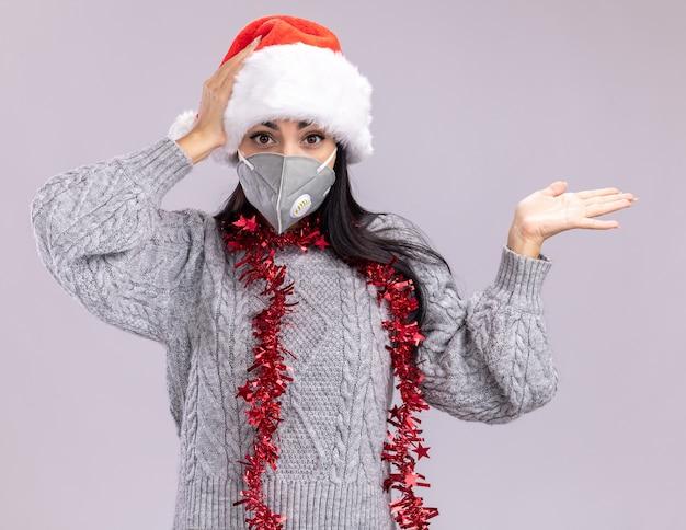 Zaniepokojona młoda kaukaska dziewczyna ubrana w świąteczny kapelusz i świecącą girlandę na szyi z maską ochronną pokazującą pustą rękę trzymającą drugą rękę na głowie odizolowaną na białej ścianie