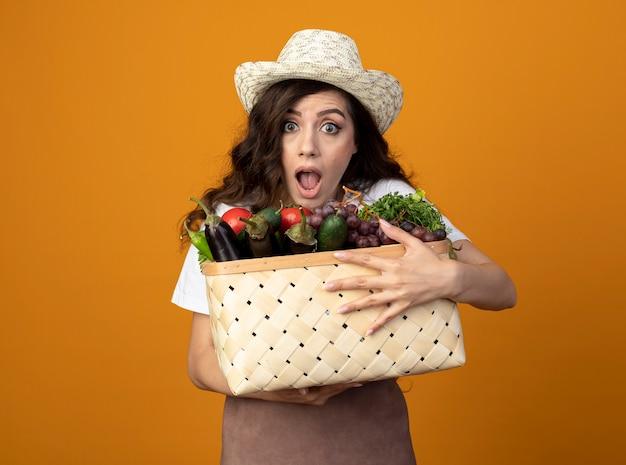 Zaniepokojona młoda kobieta ogrodnik w mundurze na sobie kapelusz ogrodniczy trzyma kosz warzyw na pomarańczowej ścianie