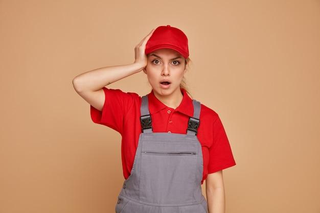 Zaniepokojona młoda kobieta pracownik budowlany w mundurze i czapce, trzymając rękę na głowie