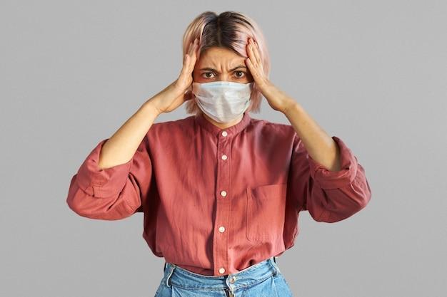 Zaniepokojona młoda kobieta rasy kaukaskiej trzymająca się za ręce na głowie, uderzona paniką, nosząca jednorazową ochronną maskę na twarz przed chorobami układu oddechowego, chorobami zakaźnymi lub emisjami przemysłowymi