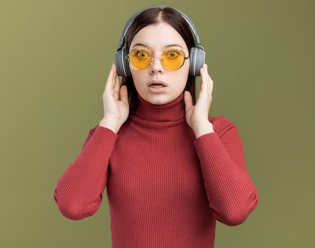 Zaniepokojona młoda ładna dziewczyna nosi okulary przeciwsłoneczne i słuchawki dotyka słuchawek