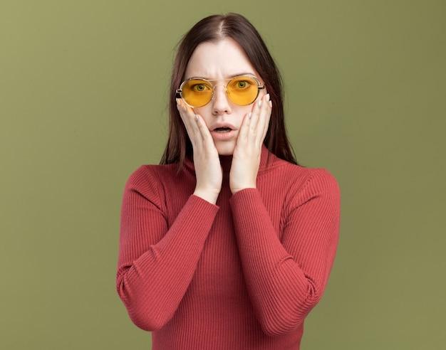 Zaniepokojona młoda ładna dziewczyna nosi okulary przeciwsłoneczne trzymając ręce na twarzy