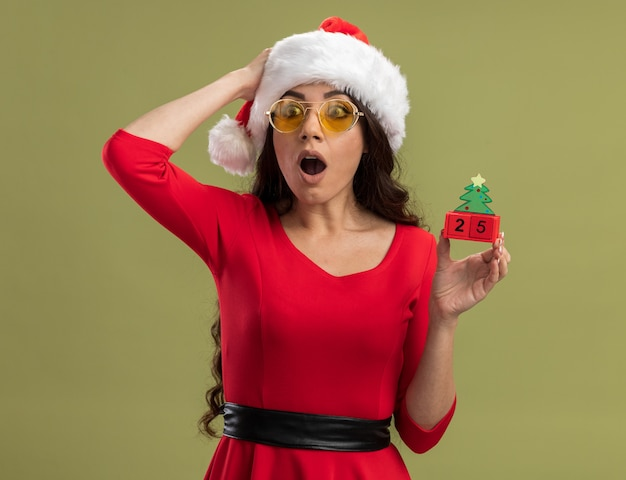 Zaniepokojona młoda ładna dziewczyna ubrana w santa hat i okulary trzymająca zabawkę choinkową z datą trzymającą rękę na głowie patrzącą na bok odizolowaną na oliwkowozielonej ścianie