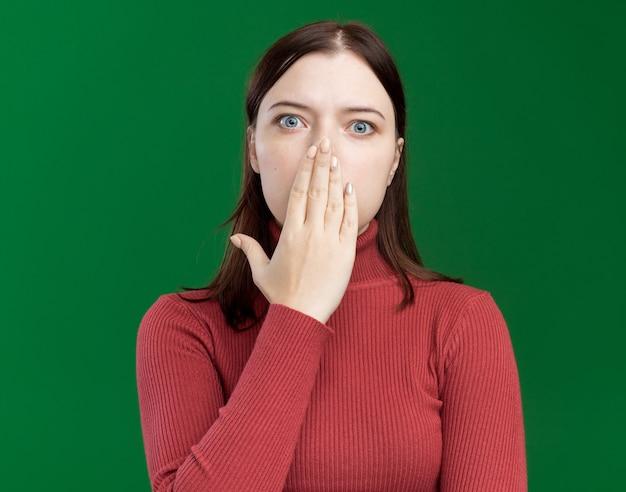 Zaniepokojona młoda ładna kobieta kładzie rękę na ustach