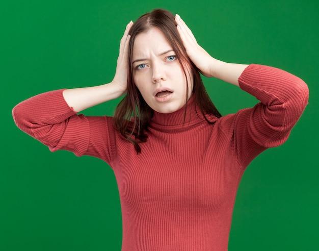 Zaniepokojona młoda ładna kobieta patrząca na przód trzymająca ręce na głowie odizolowana na zielonej ścianie