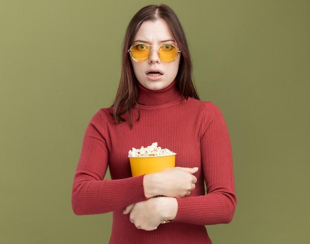 Zaniepokojona młoda ładna kobieta w okularach przeciwsłonecznych, przytulająca wiadro popcornu