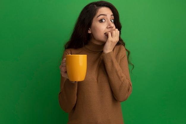 Zaniepokojona młoda piękna dziewczyna trzyma kubek herbaty gryzie paznokcie na białym tle na zielonej ścianie