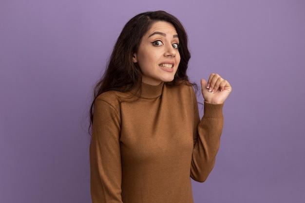Zaniepokojona młoda piękna dziewczyna ubrana w brązowy sweter z golfem wskazuje z tyłu na białym tle na fioletowej ścianie z miejsca na kopię