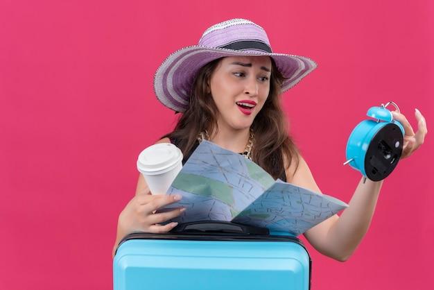 Zaniepokojona młoda podróżniczka ubrana w czarny podkoszulek w kapeluszu, trzymając budzik i mapę na czerwonej ścianie