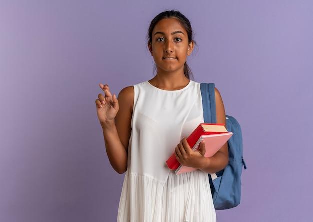 Zaniepokojona młoda uczennica na sobie plecak, trzymając książkę z notatnikiem i skrzyżowanymi palcami