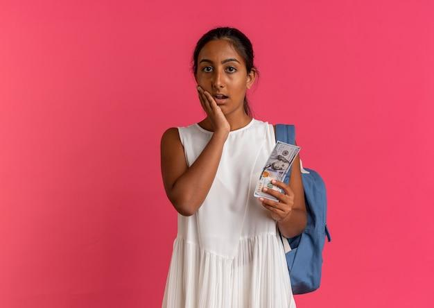 Zaniepokojona młoda uczennica w plecaku trzymająca gotówkę i kładąca dłoń na policzku