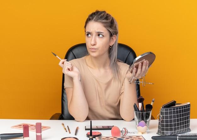 Zaniepokojona patrząc młoda piękna dziewczyna siedzi przy stole z narzędziami do makijażu, trzymając pędzel do makijażu z lustrem na białym tle na pomarańczowej ścianie