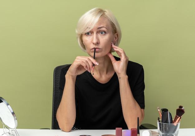 Zaniepokojona, patrząc na bok młoda piękna dziewczyna siedzi przy stole z narzędziami do makijażu, kładąc pędzel do makijażu na ustach odizolowaną na oliwkowozielonej ścianie