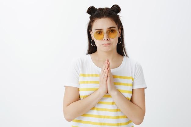 Zaniepokojona poważna młoda kobieta z okularami przeciwsłonecznymi na białej ścianie