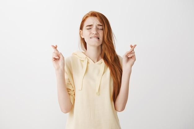 Zaniepokojona ruda dziewczyna krzyżuje palce, jednocześnie wyrażając nadzieję