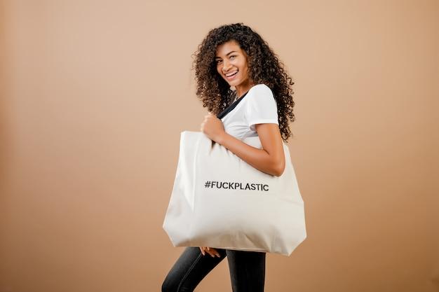 Zaniepokojona tysiącletnia czarna kobieta z ekologicznym kurwa plastikową wiadomością na torbie na brązowym tle