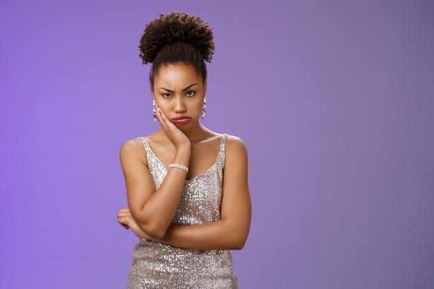 Zaniepokojona zdenerwowana afro-amerykańska kobieta czeka w toalecie w klubie nocnym w srebrnej modnej sukience zmęczona stojąca kolejka co trwa tak długo dąsając się marszcząc brwi nastrojowy trzymać rękę podrażniony policzek, niebieskie tło.