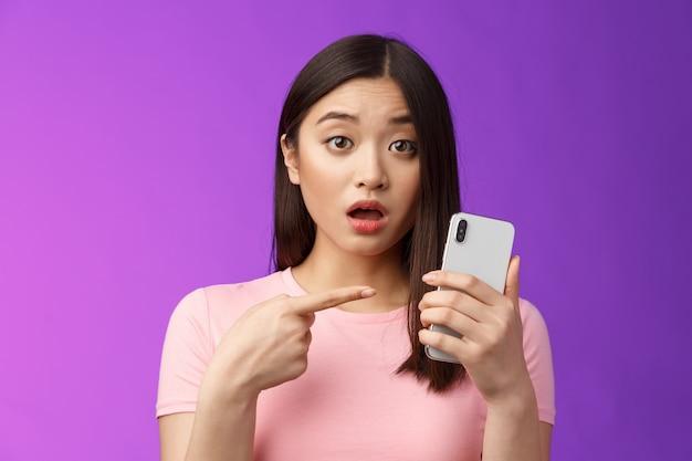 Zaniepokojona zdezorientowana śliczna młoda azjatycka kobieta trzyma smartfona otwarte usta, wskazując palcem telefon, wygląda na zakwestionowanego zdenerwowanego, zmartwionego patrz dziwny post online, stoi na fioletowym tle. skopiuj miejsce