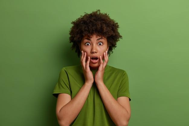 Zaniepokojona zdumiona ciemnoskóra kobieta chwyta twarz, wstrzymuje oddech, nosi zwykłe ubranie, martwi się o coś, odizolowana na zielonej ścianie. bezmowa, pod wrażeniem kobiety, widzi coś niesamowitego