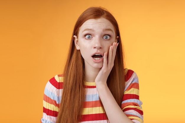 Zaniepokojona zmartwiona ruda dziewczyna niebieskie oczy opadają szczęki, sapanie dotyk policzek zdezorientowany wyglądając na nerwowo zaniepokojonego, okazuje empatię słysząc okropną denerwującą historię stojącą na pomarańczowym tle. skopiuj miejsce