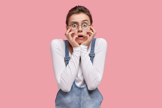 Zaniepokojona, zszokowana młoda uczennica w panice dotyka policzków, ma szeroko otwarte oczy, ubrana w modne ciuchy