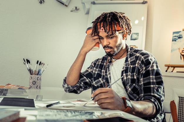 Zaniepokojony artysta. ciemnowłosy artysta z dredami czuje się zaniepokojony tym, że ma za dużo pracy