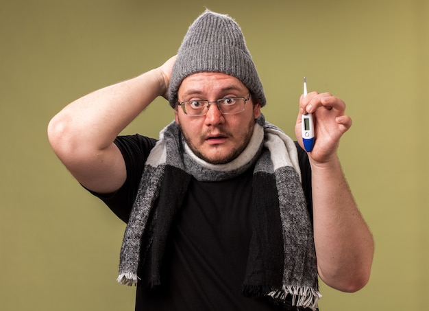 Zaniepokojony chory mężczyzna w średnim wieku noszący czapkę zimową i szalik trzymający termometr kładący rękę na głowie