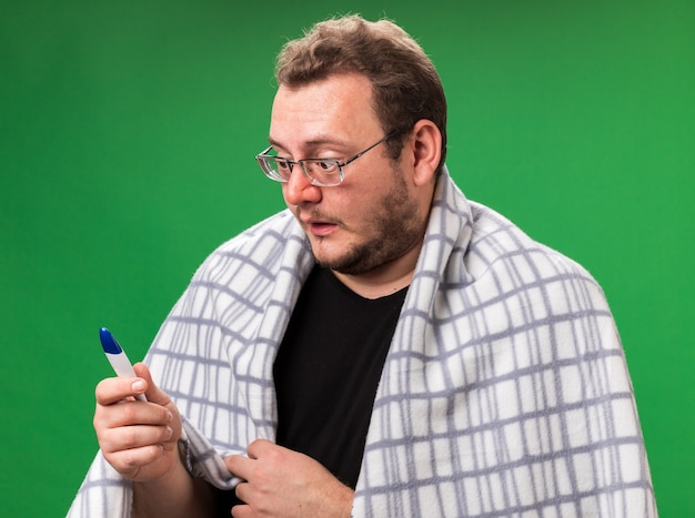 Zaniepokojony chory mężczyzna w średnim wieku owinięty w szkocką kratę i patrzący na termometr