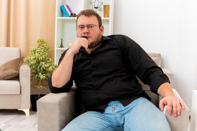 Zaniepokojony dorosły słowiański mężczyzna w okularach optycznych siedzi na fotelu, trzymając pilota do telewizora na ustach i patrząc na kamerę w salonie