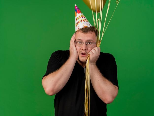 Zaniepokojony dorosły słowiański mężczyzna w okularach optycznych w czapce urodzinowej kładzie ręce na twarzy trzymając balony z helem