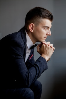 Zaniepokojony fornal bawić się rękami i patrzeje z boku podczas gdy będący ubranym smoking, siedzi na czarnym pracownianym tle