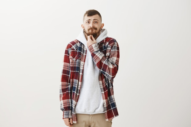 Zaniepokojony i zmartwiony hipster facet dotykający brody i pochylony przestraszony