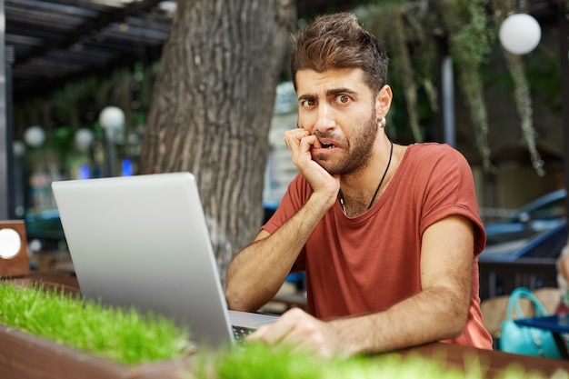 Zaniepokojony i zmartwiony mężczyzna obgryzający paznokcie i wyglądający na zdenerwowanego popełnił błąd podczas pracy z laptopem na pilocie, z kawiarni na świeżym powietrzu lub przestrzeni coworkingowej
