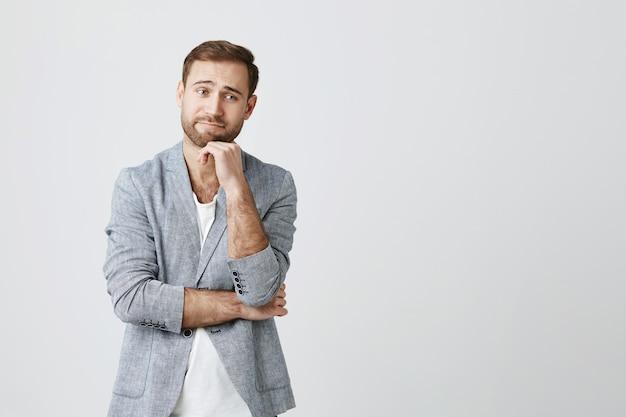 Zaniepokojony lub niezręczny mężczyzna unika kontaktu wzrokowego