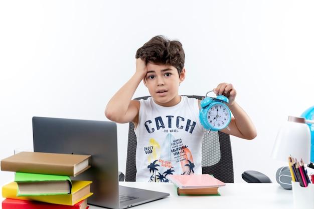 Zaniepokojony mały uczeń siedzi przy biurku z narzędziami szkolnymi, trzymając budzik i złapał głowę na białym tle