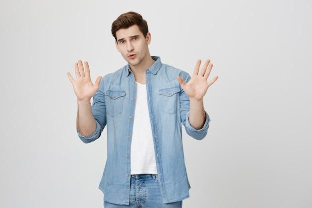 Zaniepokojony mężczyzna pokazujący gest zatrzymania, odrzucający złą ofertę