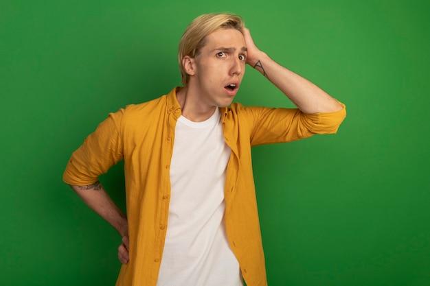 Zaniepokojony młody blondyn ubrany w żółtą koszulkę kładąc rękę na głowie na białym tle na zielono