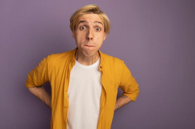 Zaniepokojony młody blondyn ubrany w żółtą koszulkę kładzie ręce na talii